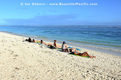 backpackers sunbathing on our beach in rarotonga